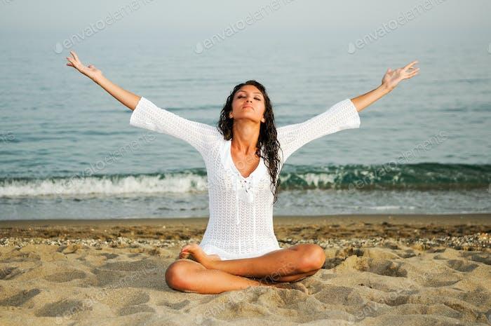 Hübsche Frau tun Yoga am Strand