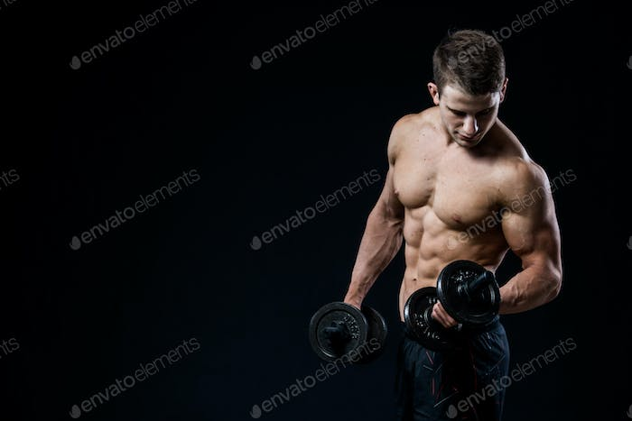 Handsome power athletic man training pumping up muscles with dumbbells in a gym. Fitness muscular