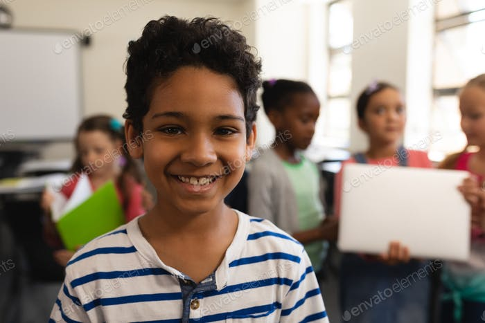 Close-up of happy schoolboy looking at camera in classroom of elementary school