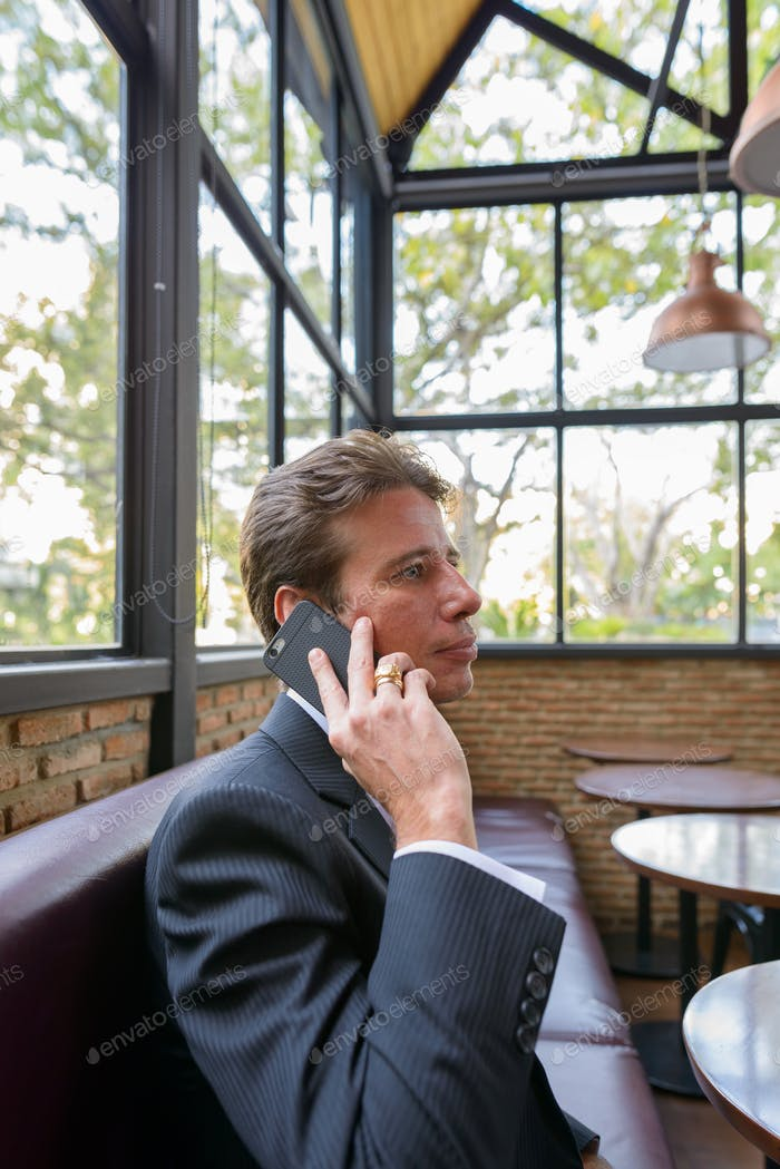 Profile view of businessman talking on mobile phone in coffee shop
