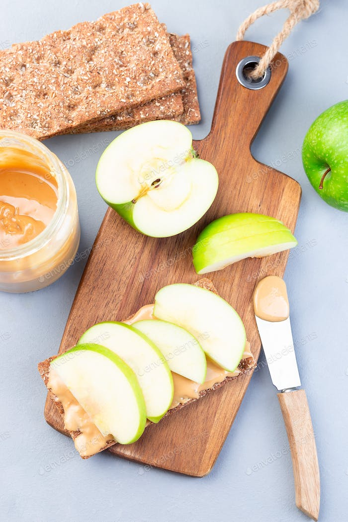 Sandwich with whole grain cracker, green apple slices, peanut butter