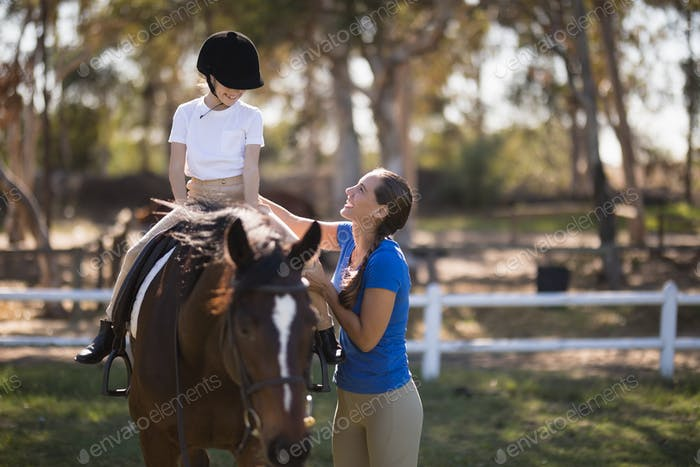 Side view of happy female jockey teaching girl