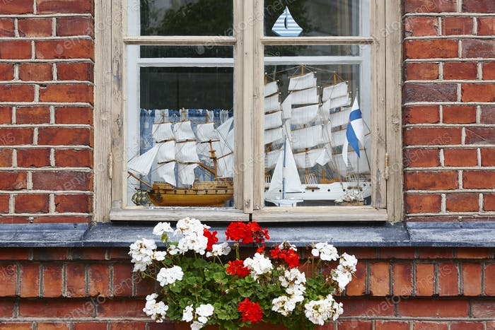 Old brick facade with wooden window and model yachts. Horizontal