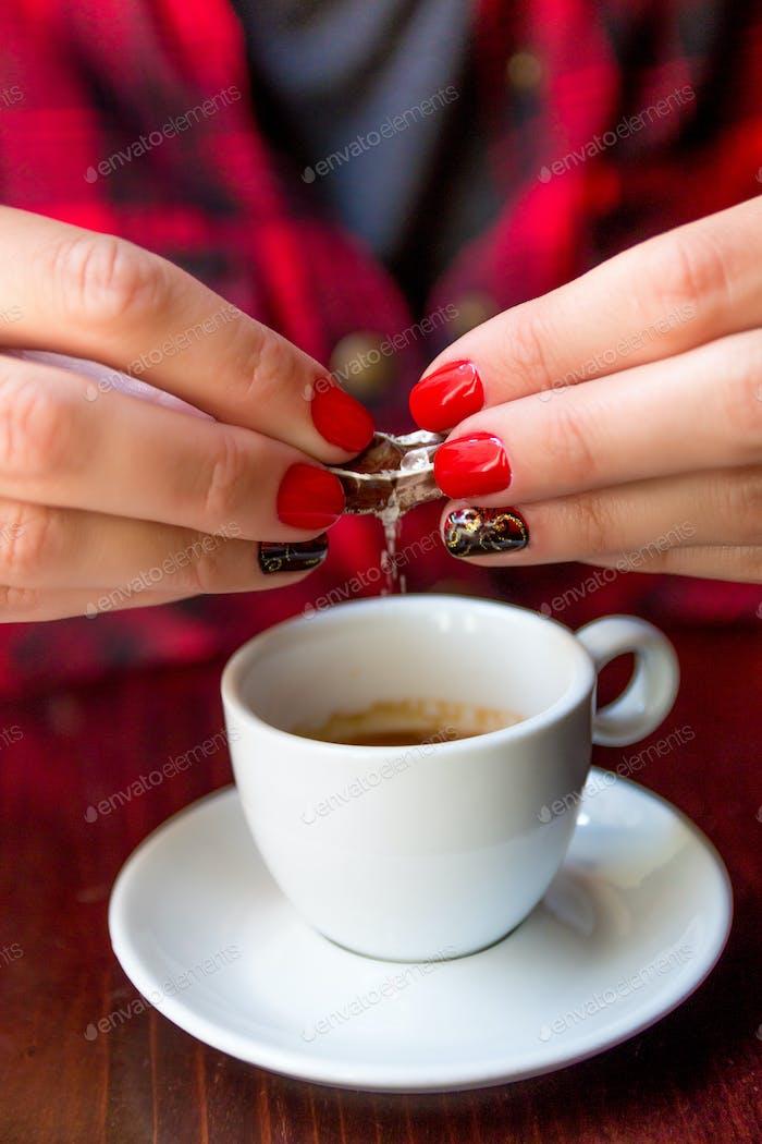 Cerca de la Mano de la Mujer con uñas pulidas rojas y negras es Caída de azúcar en un café espresso