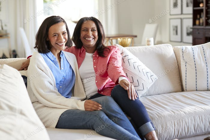 Young adult woman sitting on the sofa in living room with her mother smiling to camera