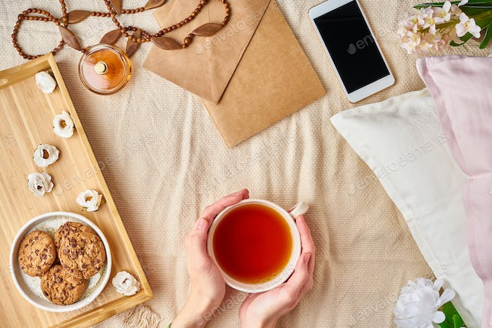 Woman holding mug of hot tea. Lazy cozy morning in bed. Flat lay woman accessories