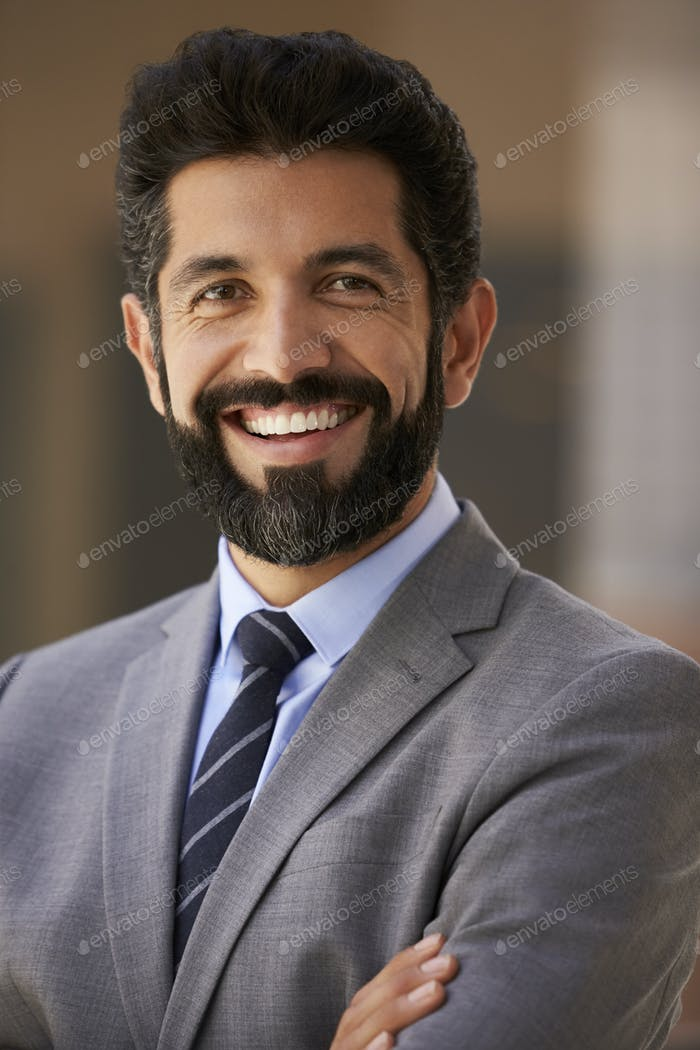 Middle aged Hispanic businessman smiling to camera, close up