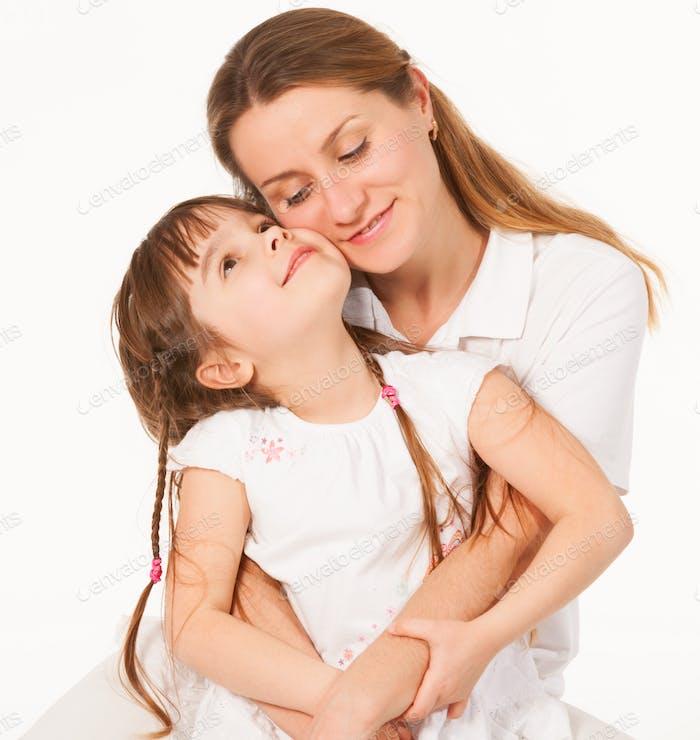 Mother hugs her charming smiling little girl