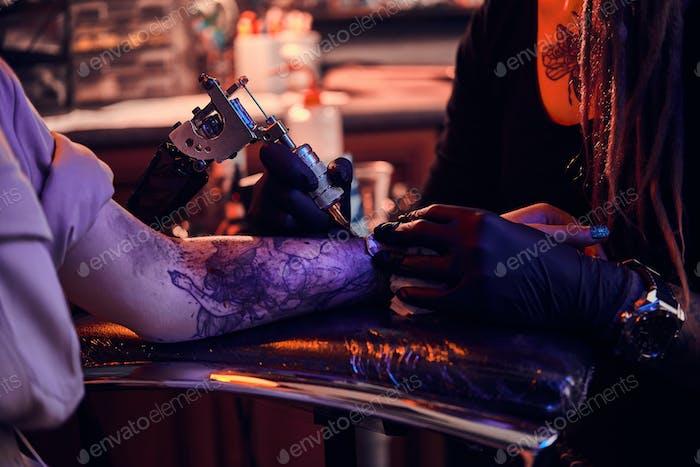 Process of tattoo makining at dark tattoo studio.