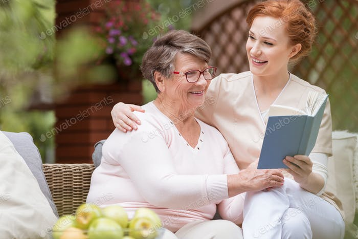 Cheerful senior woman with her tender caretaker reading a book t