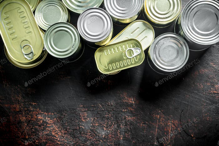 Assortment of various closed tin cans with canned food.