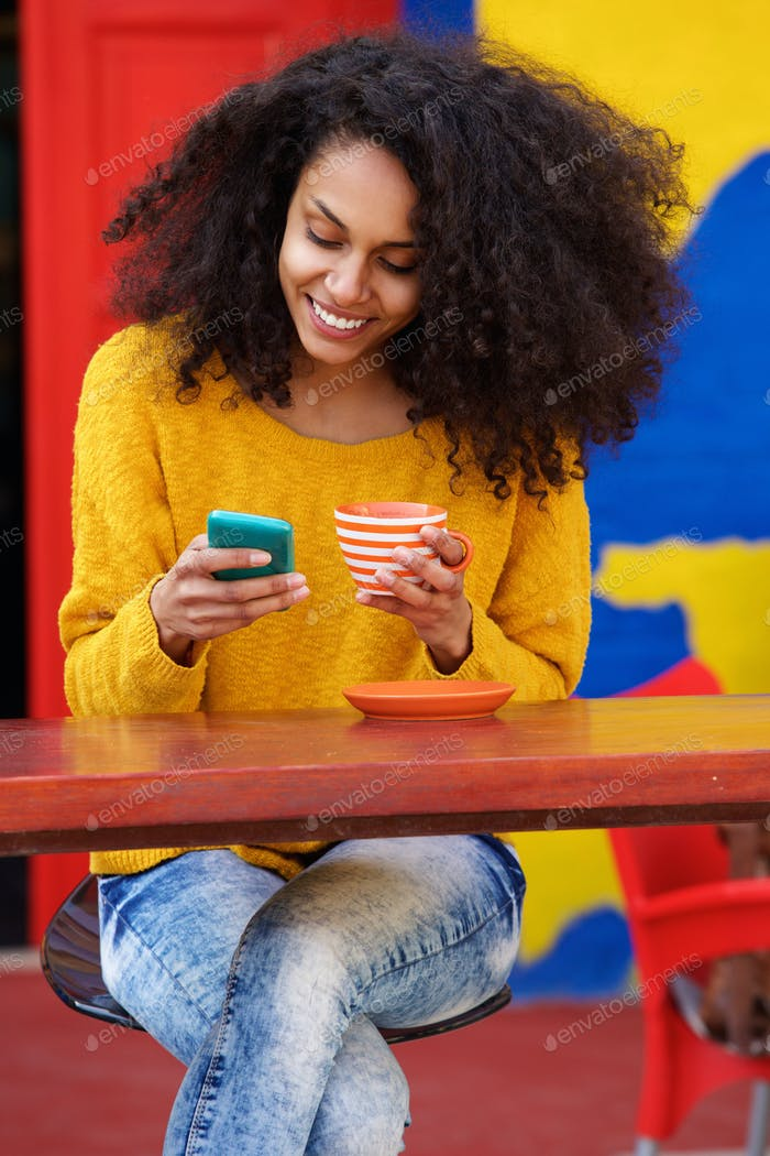 Relaxed young woman using mobile phone at coffee shop