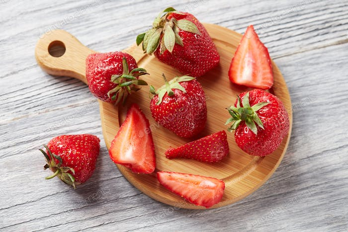 Slices and whole ripe strawberries on a wooden board on a gray wooden background. Healthy vtamin