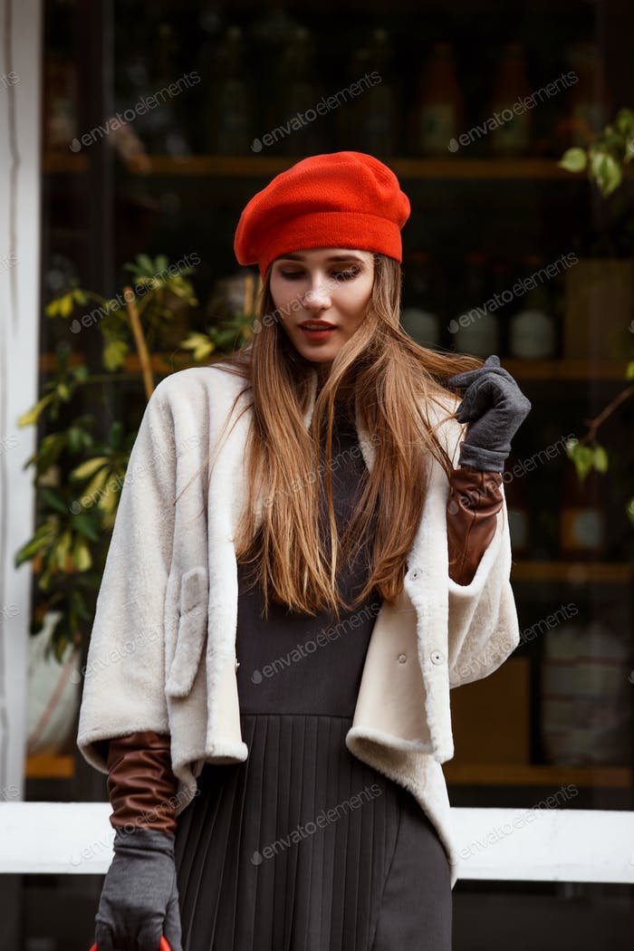 Fashionable girl dressed in stylish gray dress, short sheepskin coat, gloves and red beret walks in