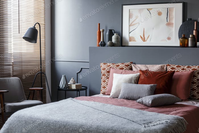 Creative poster on black bedhead above cozy bed with decorative