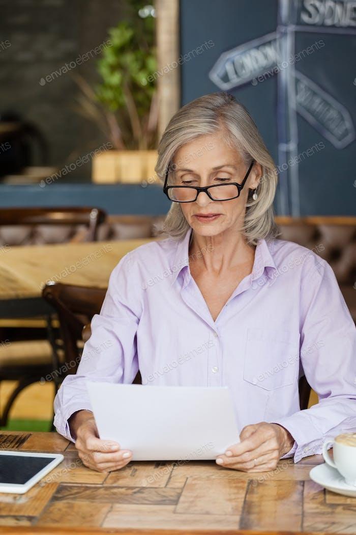 Senior woman using tabletv while sitting at table