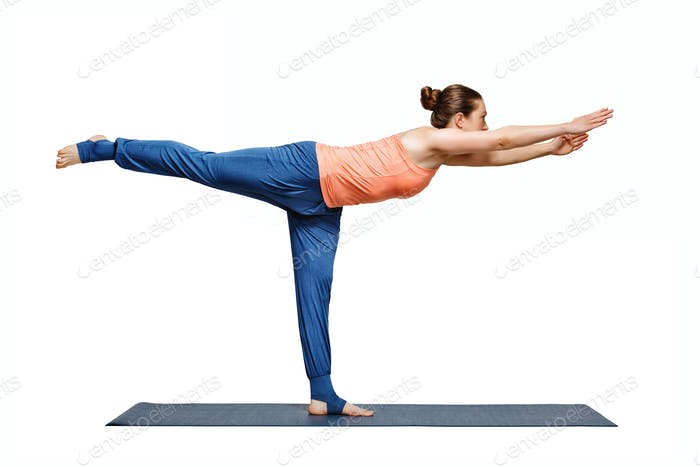 Sporty fit yogini woman practices yoga asana utthita Virabhadras