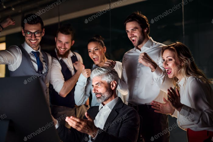A group of business people in an office at night, expressing excitement