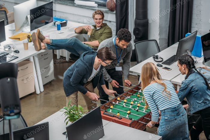 multiethnic colleagues playing in table soccer at modern office