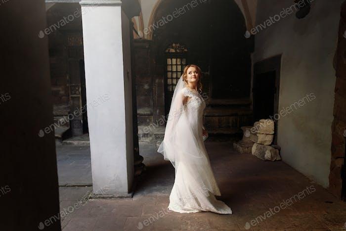 Schöne blonde Braut in eleganten weißen Hochzeitskleid posiert in der alten europäischen Straße