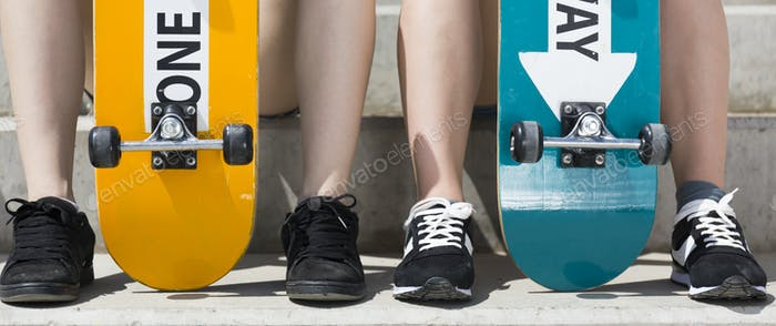 Skateboards between teenagers legs