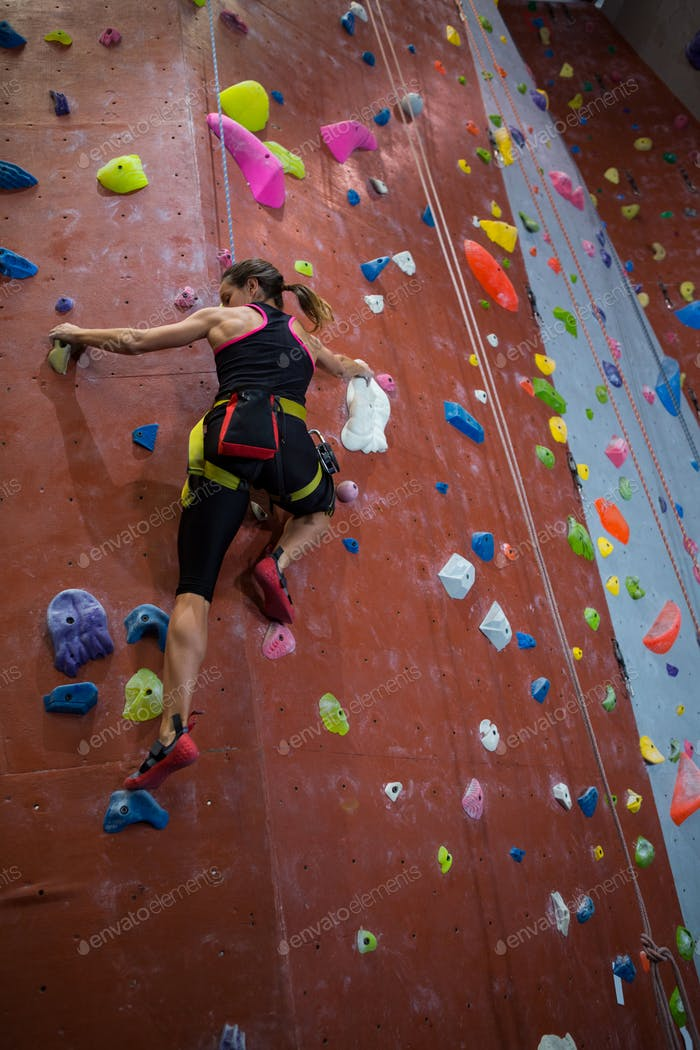 Woman practicing rock climbing in fitness studio