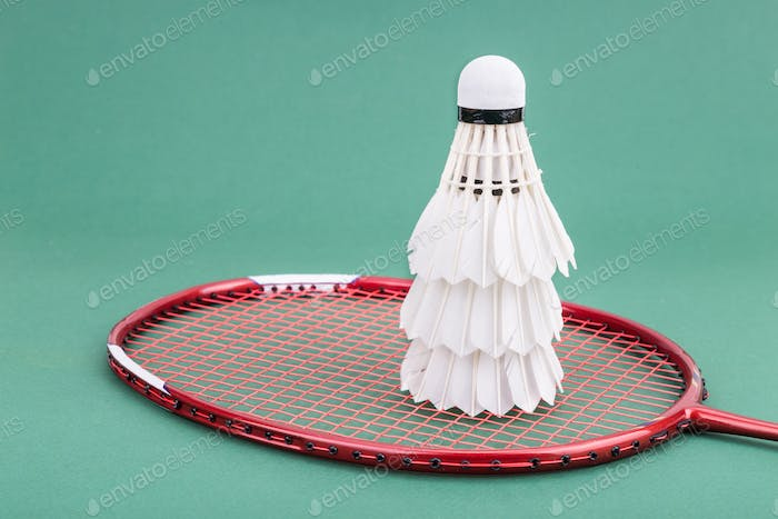 Three new badminton shuttlecock with rackets on green mat court