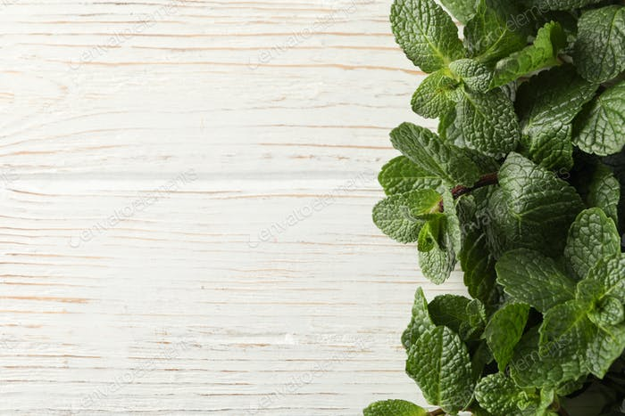 Frame of mint on wooden background, space for text