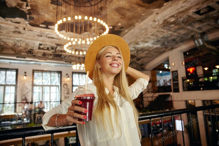 Pleased attractive long haired blonde lady standing over restaurant interior