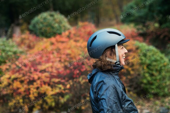 A side view of active senior woman with bicycle helmet standing outdoors in nature.