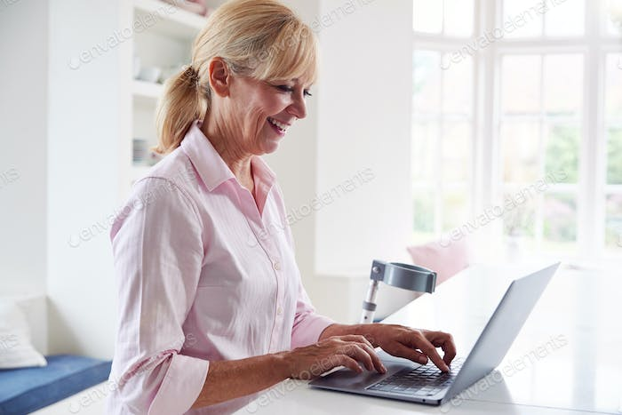 Mature Disabled Woman With Crutches At Home Working On Laptop On Kitchen Counter