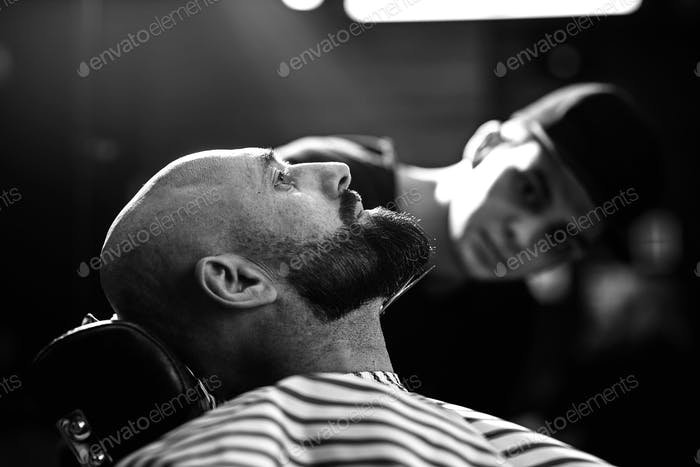Black and white photo. Fashion barber dressed in a black clothes tidies up men's beard and