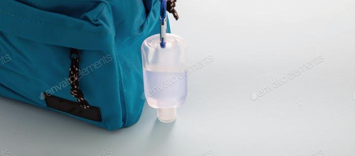 Back to school, coronavirus days, sanitizer gel on a blue color backpack,