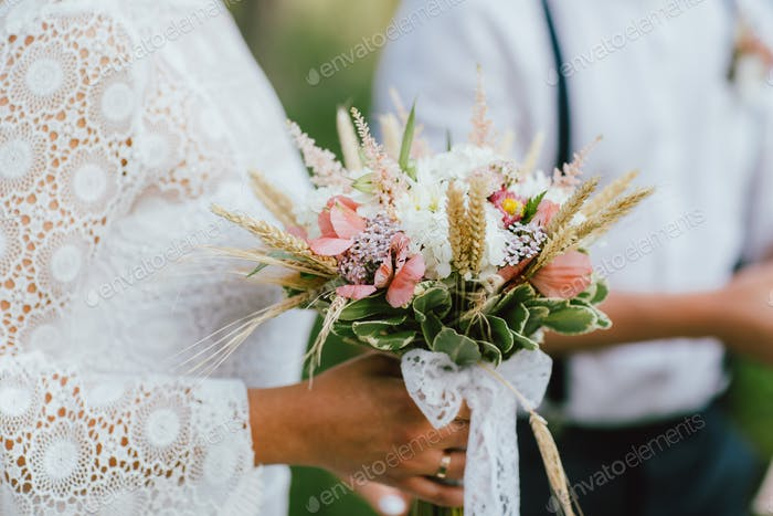 Crop photo of bride young woman with the boho style bouquet with groom on wedding