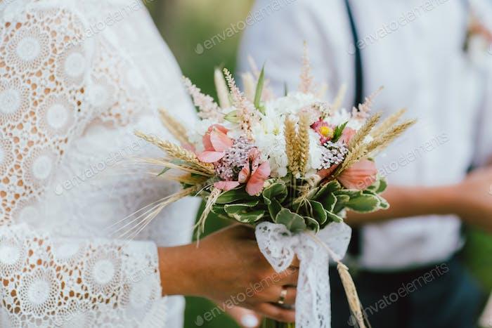 Crop Foto der Braut junge Frau mit dem Boho Stil Blumenstrauß mit Bräutigam auf Hochzeit