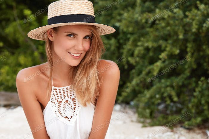 Shot of beautiful female tourist recreats on beach in tropical country, has positive expression, sat