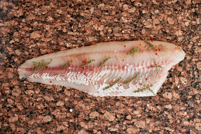 Fresh raw pike perch fish fillet on marble dark brown table. Top view
