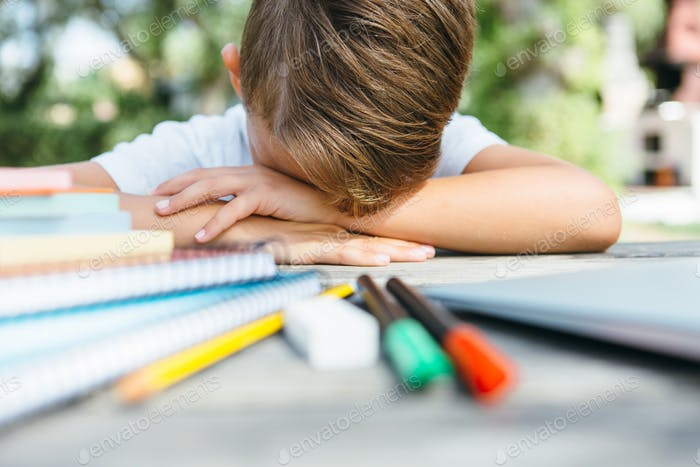Exhausted schoolboy with notebooks