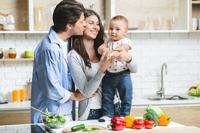 Young parents embracing with baby son at kitchen