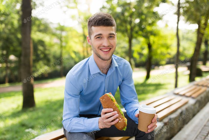 Young cheerful man in blue shirt sitting on bench with cup of co