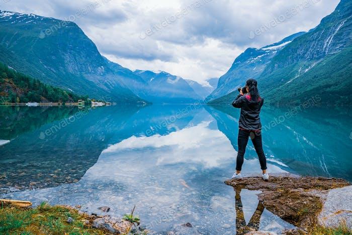Nature photographer tourist with camera shoots lovatnet lake Bea