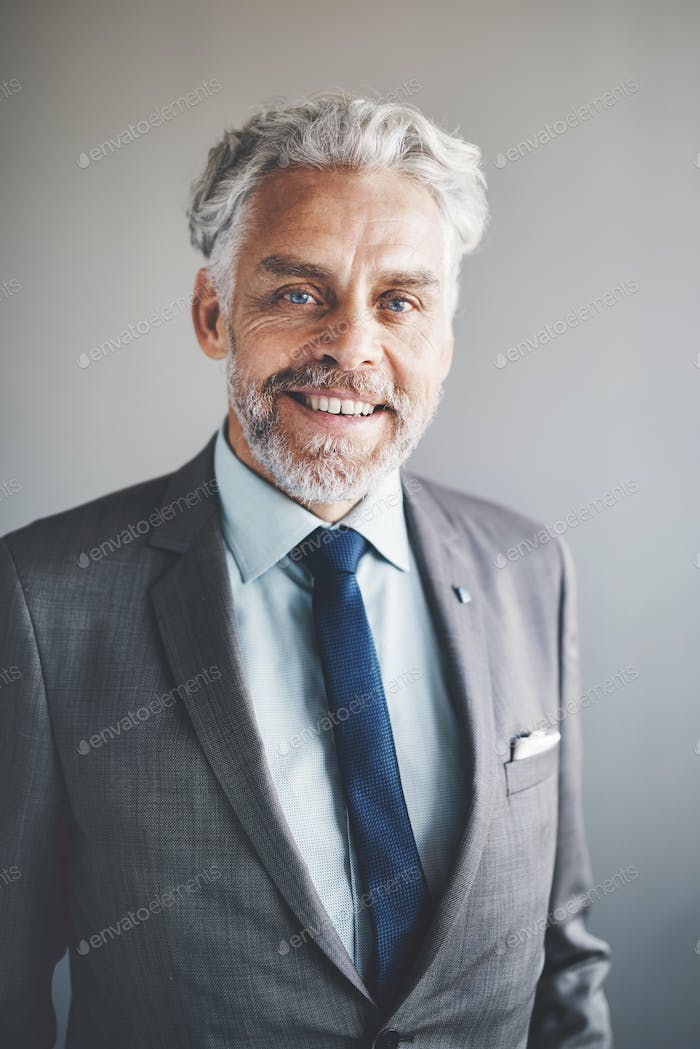 Mature corporate executive wearing a suit and smiling confidently