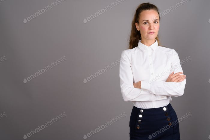 Young beautiful businesswoman against gray background