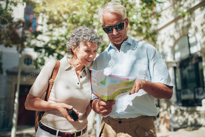 Senior couple looking at a map while sightseeing