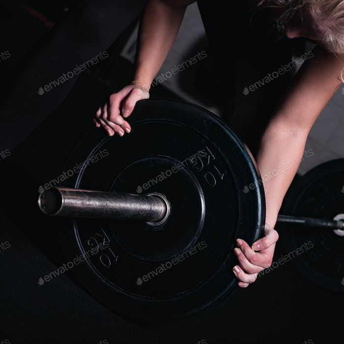 Sporty Woman With Barbell In A Gym