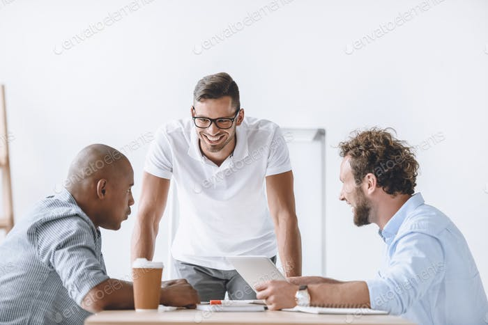 multiethnic group of businessmen having discussion at meeting in office