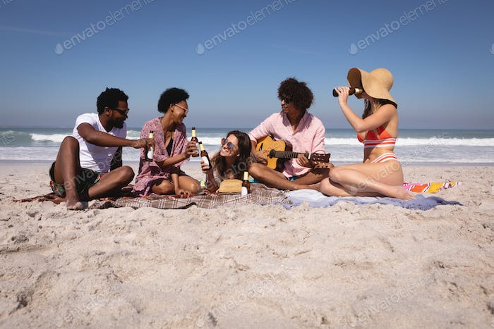 Happy diverse group of friends having fun and drinking beer while sitting on blanket at beach