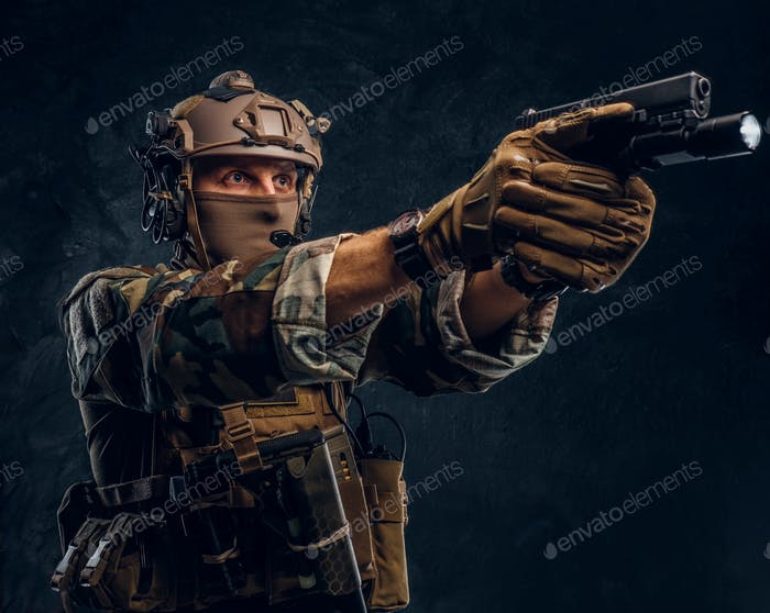 Special forces soldier in camouflage uniform holding a gun with a flashlight