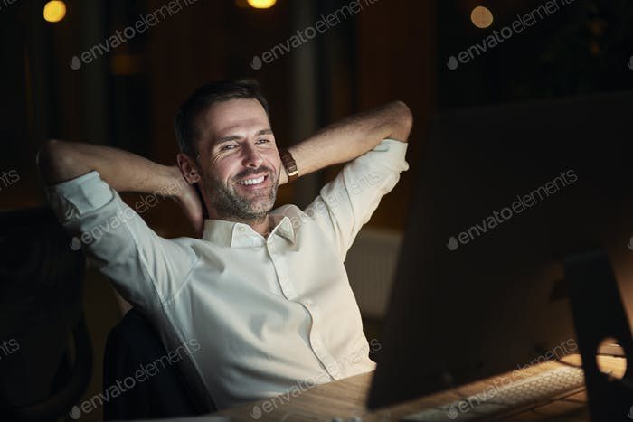 Satisfied businessman resting in his office