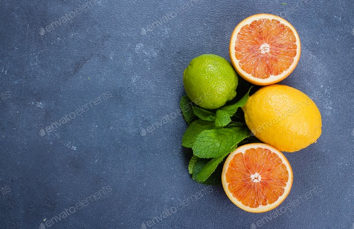 Lime, lemon and red orange with mint on table. Ingredients for mojito preparing or lemonade